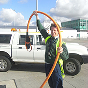 Photograph of an airport worker holding a thick orange cable aloft